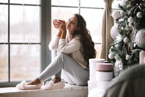 A woman dressed in comfy clothes and fuzzy slippers sits on a windowsill and holds a red mug at a bed and breakfast over the holidays.