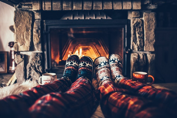 Two people wearing flannel PJs and cozy socks sit next to the fireplace in a bed and breakfast over the holidays.