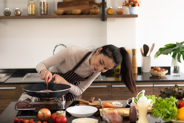 A brunette woman wearing a turtleneck and apron cooks a meal in her kitchen.