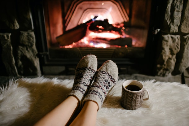 A woman in wool socks relaxes her feet next to a fireplace, blanket, and cup of hot tea in a cabin.