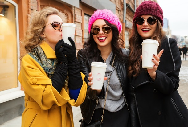 Outdoors fashion portrait of three young beautiful women friends drinking coffee. Smiling and going shopping. Kissing a cup of coffee. Wearing stylish outerwear, hats and sunglasses. Bright make up