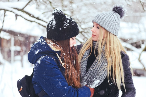funny and happy two beautiful girlfriends play in the snow in winter, a lot of snow and winter clothes. blonde and brunette caring and emotions.