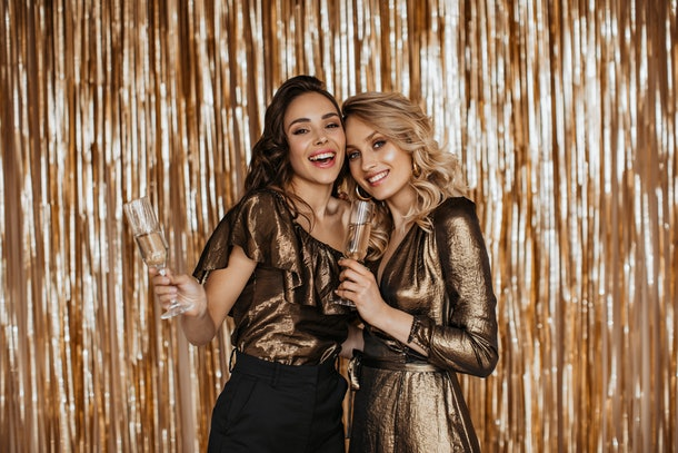 Two friends at a party smile and hold up their champagne flutes in front of a gold backdrop on New Year's Eve.
