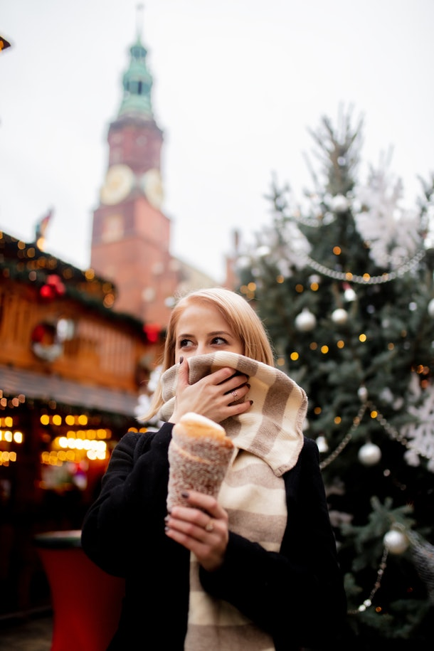 A blonde woman holds a sugary treat in a holiday market while covering her face with her scarf in a Christmas town in the U.S.