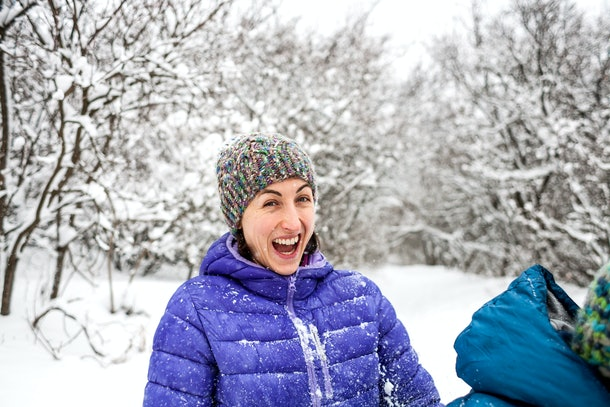 The girl plays snowballs. Emotional woman having fun with friends in a winter park. Walk through the snowy forest. Winter fun.