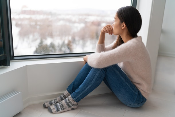 Depressed young girl feeling sad an lonely, anxious looking out the window in winter. Unhappy Asian woman alone, depression at home.