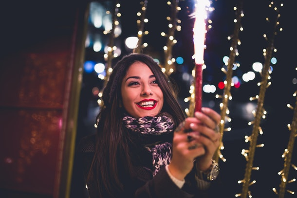 Beautiful young brunette woman with Jack Russel terrier enjoying Christmas or New Year night on a city street.