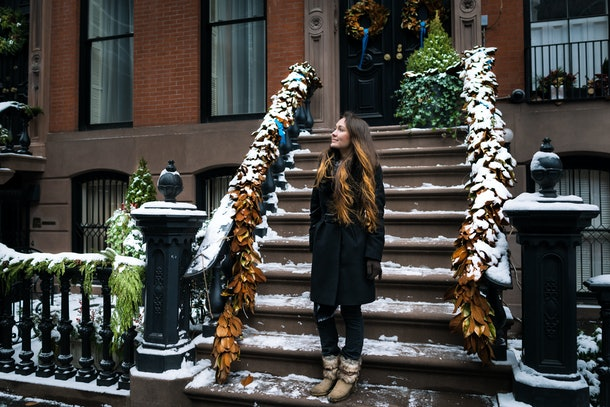 A brunette woman looks up and stands on snowy steps of a NYC apartment in the winter.