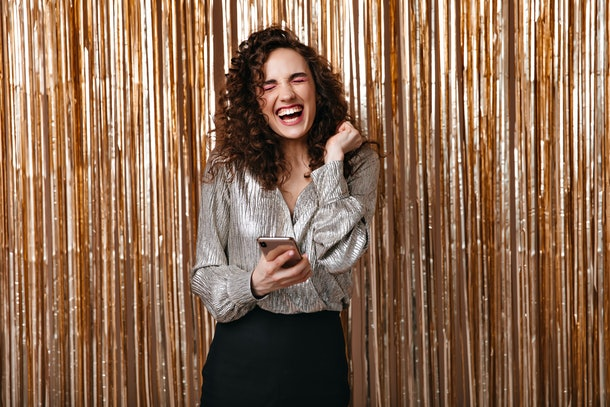 Positive girl in silver outfit holding phone and laughing