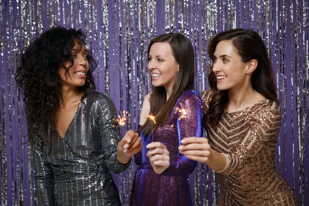 Women in fancy sparkling dresses posing isolated over vibrant purple violet silver background. Positive people spending time on happy birthday new year holiday party discotheque hold burning sparkler