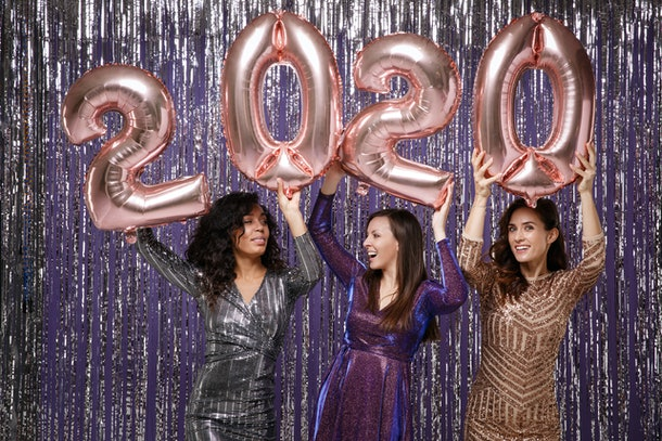 women in fancy sparkling dresses posing isolated over vibrant purple violet silver background. Positive people spending time on happy new year holiday party discotheque, hold inflatable figures 2020