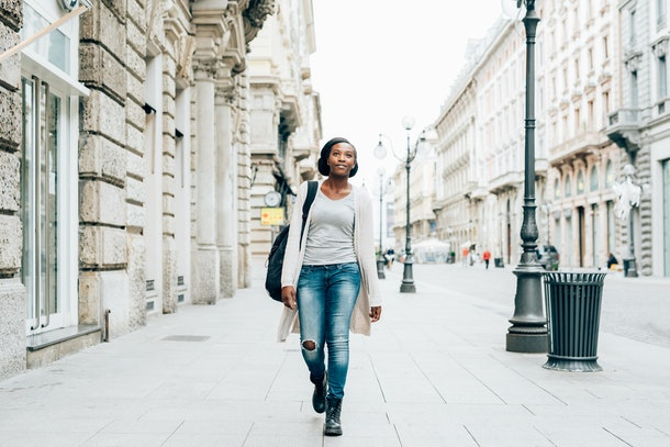 A woman in a long cardigan and jeans walks down a city street during the winter.