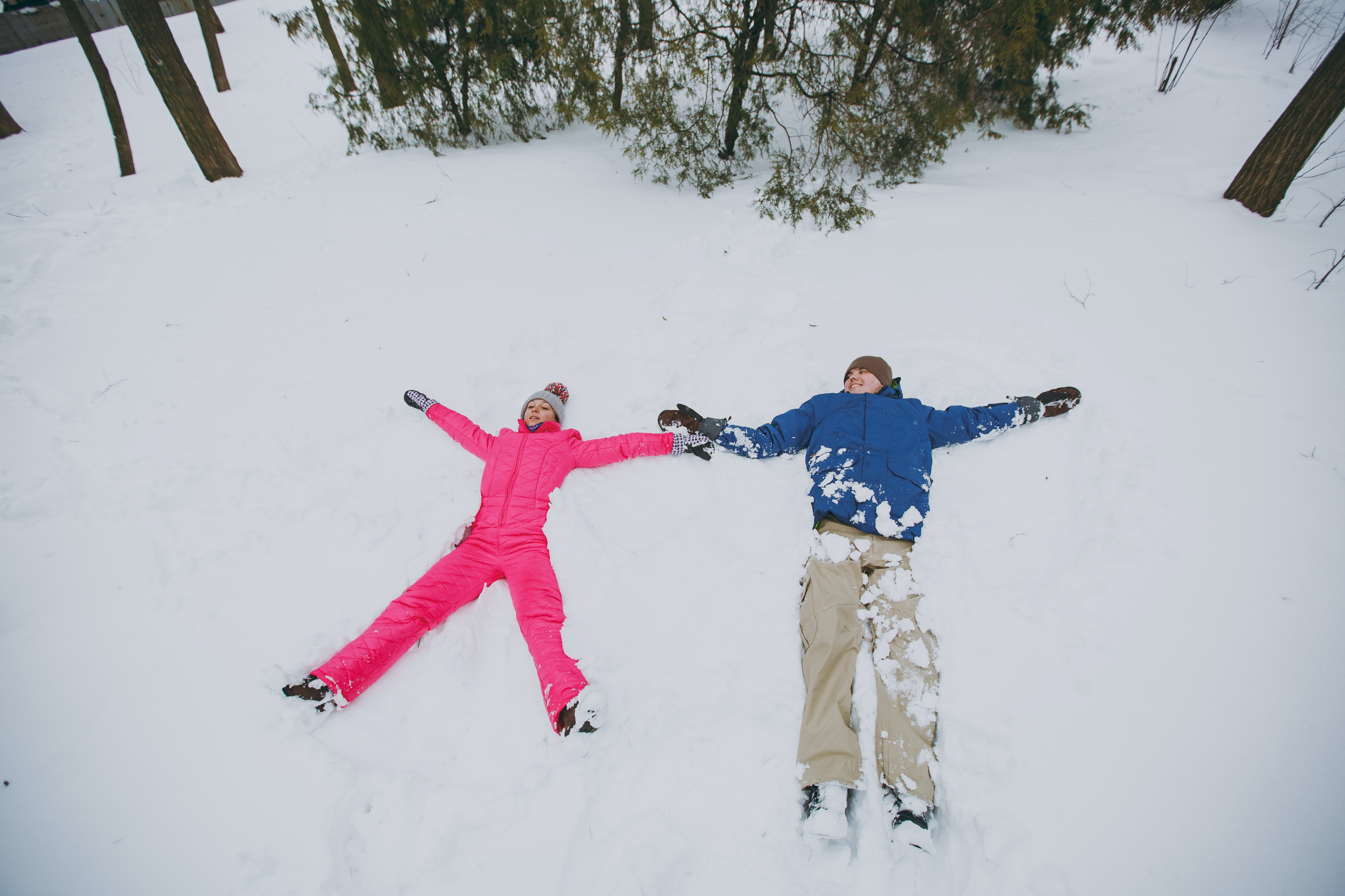 Happy couple woman and man in colorful winter warm clothes making snow angels while lying in park or forest outdoors. Winter fun leisure on holidays. Love relationship family people lifestyle concept