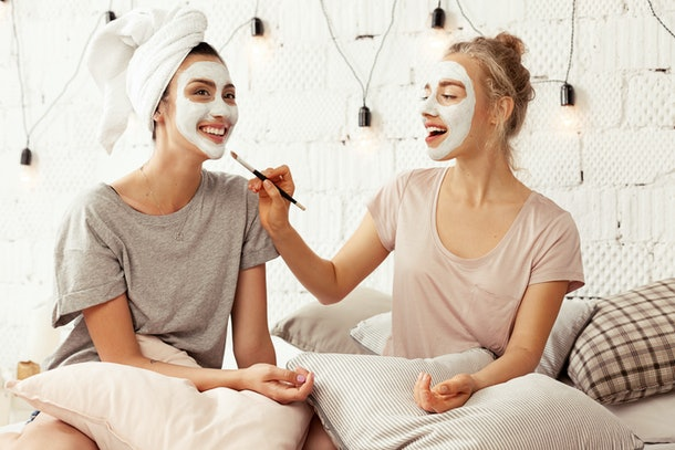 Two girls do facials while hanging out in bed and smiling.