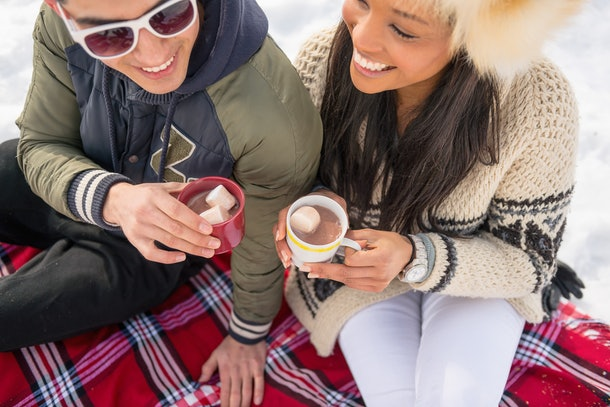 A happy couple enjoys hot chocolate on a red flannel blanket in the snow.