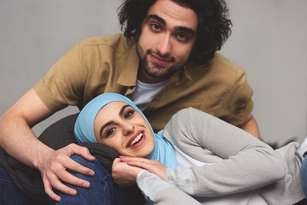 smiling muslim couple looking at camera at home