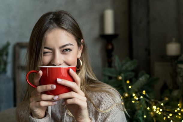 Beautiful girl drinking coffee or tea from a red cup and and winks. Christmas mood with copy space