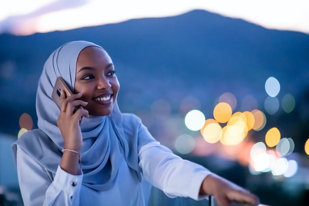 Young modern Muslim woman wearing scarf veil on urban city  street at night texting on smartphone with bokeh city light in background