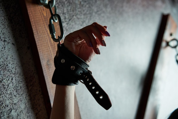 Sexual bdsm toy. Woman with hands tied. Outfit for playing bdsm games. Arrested lady with handcuffs.