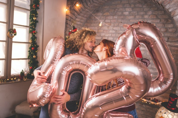 Beautiful young couple in love celebrating New Year, kissing and holding giant balloons shaped as numbers 2020, representing the upcoming holiday season