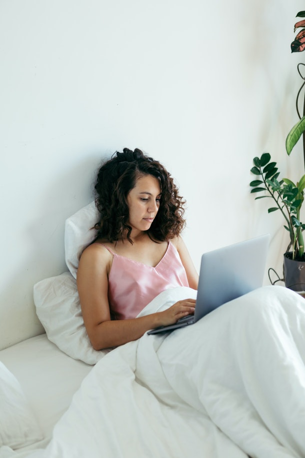 A woman sits in her bed with a laptop and creates a website.