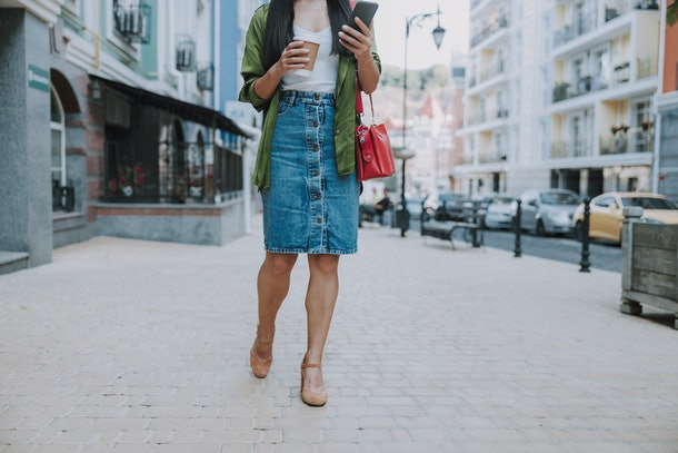 A woman in casual work attire walks down a city street with coffee in her hand.