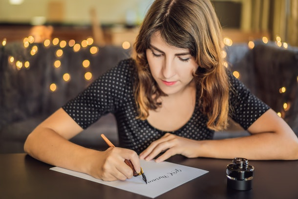 Good morning. Calligrapher Young Woman writes phrase on white paper. Inscribing ornamental decorated letters. Calligraphy, graphic design, lettering, handwriting, creation concept