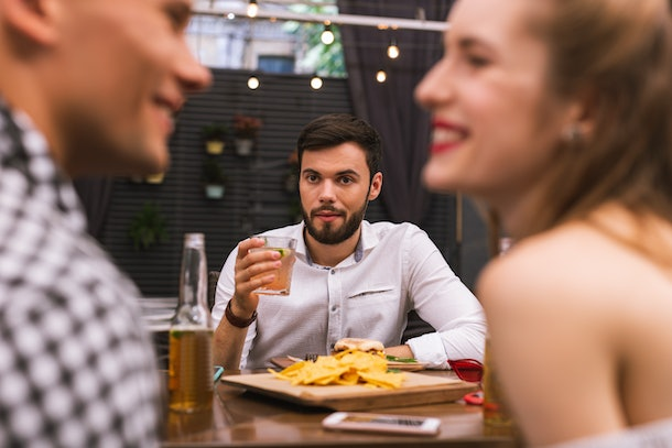 Odd friend. Calm young man thoughtfully drinking his alcohol and looking at two friends flirting