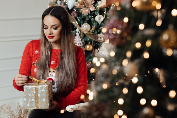 The girl holds gift box in her hands. Happy new year. Christmas. Beautiful smiling woman. Makeup. Elegant lady in sweater over christmas tree and light candles background. Happy new year holiday.