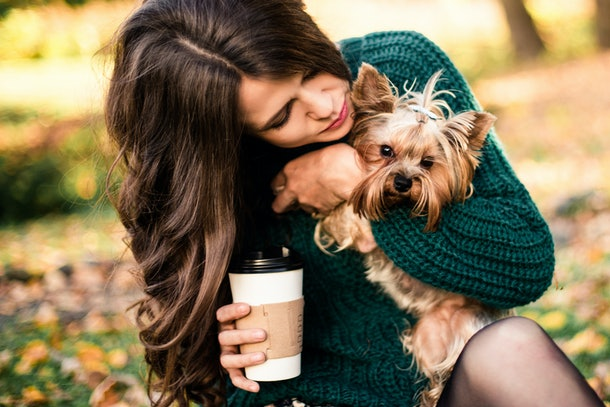 A woman walks her dog through the park with a cup of coffee in hand.