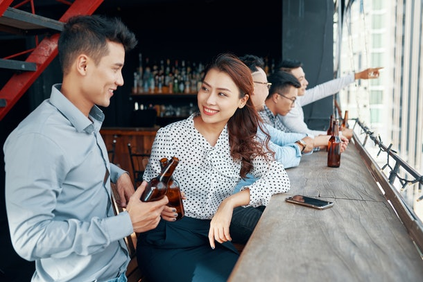 Vietnamese young man and pretty woman drinking beer and flirting in bar