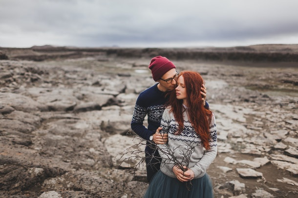 Close-up lovely portrait of young hipster couple kissing and hugging together. Traditional handmade Iceland wool sweaters, red hair and hat. Dramatic nordic stone landscape, cold weather.