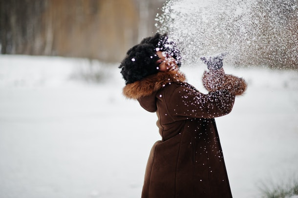 A stylish woman poses for a picture while throwing snow in the air.