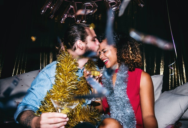 A guy kisses his smiling girlfriend on the couch on New Year's Eve in a nightclub.