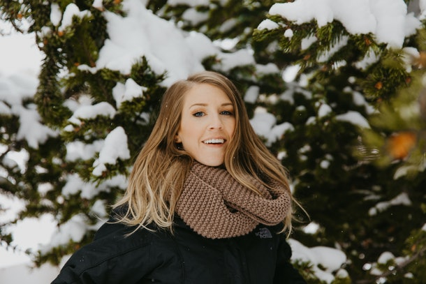 A woman in winter clothes smiles amongst evergreen trees covered in snow.