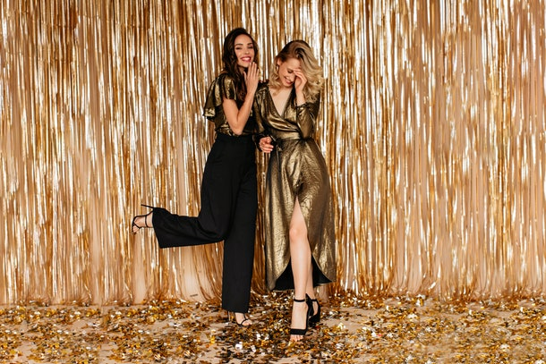 Two friends laugh and stand on gold confetti in front of a gold backdrop on New Year's Eve.