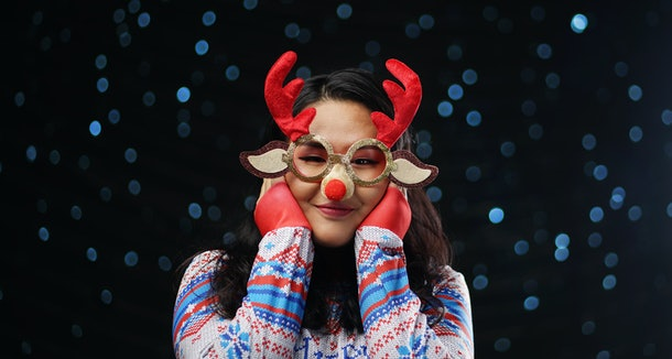 Asian Girl Wearing Christmas Sweater and Christmas Reindeer Glasses Red Nose