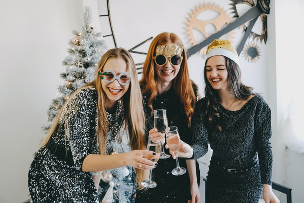Cheers! New Year Eve, Christmas Celebration. Three partying girls clinking flutes with champagne. Young beautiful women in evening dress celebrating  party, drinking wine and dancing.
