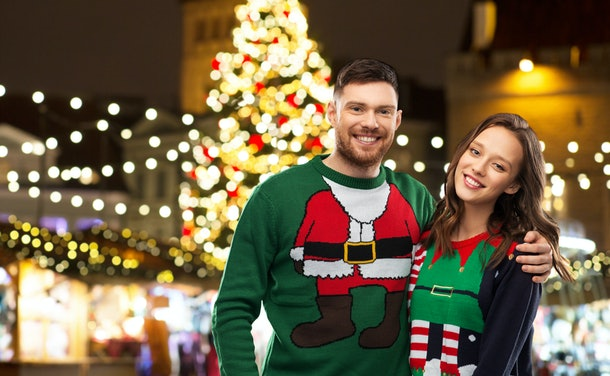 winter holidays, celebration and people concept - portrait of happy couple in ugly sweaters hugging over christmas market lights background
