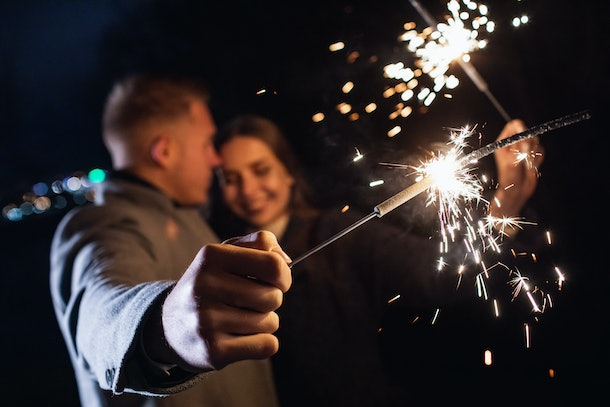 Selective focus of sparklers in hands of young couple enjoying holiday time outdoors