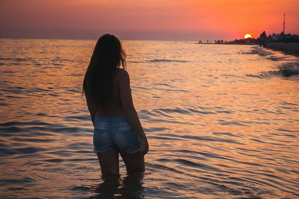 girl on a sunset background. girl and the sea. stands with his back to the sea. beautiful landscape.