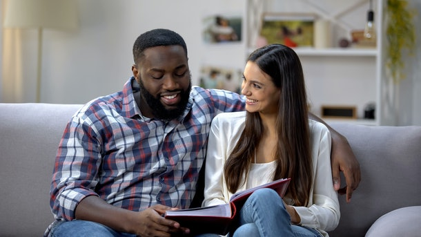Smiling multiethnic couple watching photo album at home, pleasure memories