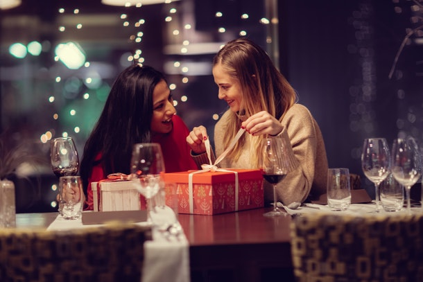two adolescent women sitting in a fancy restourant, going through the menue, while drinking some red wine, talking, gossiping and unwrapping their christmass presents and looking at their phones.
