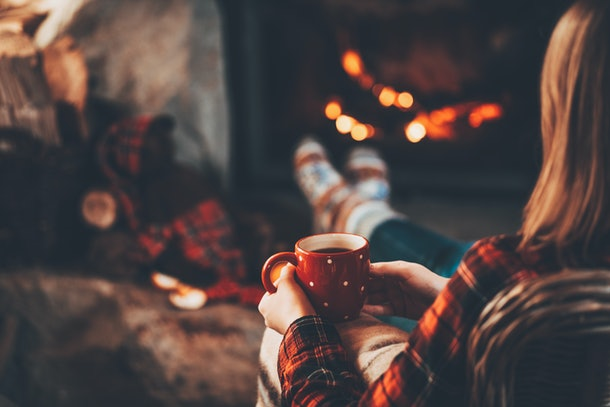 Woman and her Teddy Bear by the fireplace. Unrecognisable relaxes by warm fire with a cup of hot drink and warming up her feet in woollen socks. Cozy atmosphere. Winter and Christmas holidays concept.
