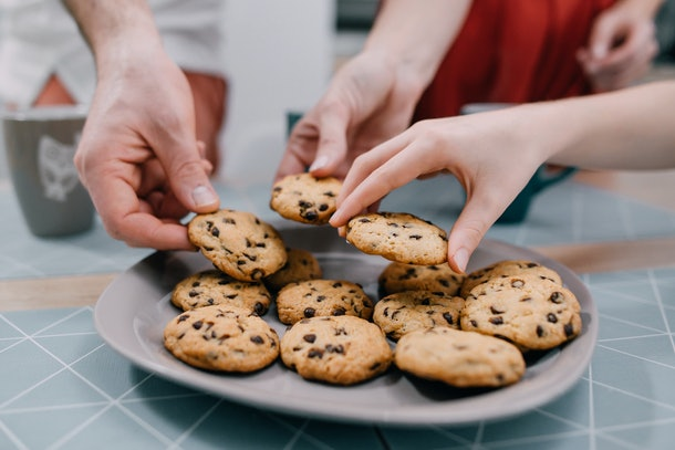 Three hands take fresh chocolate chip cookies from plate.