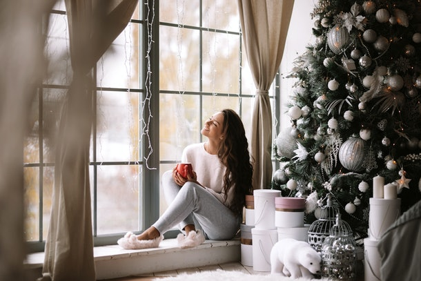 Charming dark-haired girl dressed in pants, sweater and warm slippers holds a red cup sitting on the windowsill of a panoramic window in the room next to the New Year tree, gifts and candles