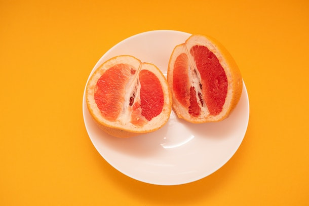 Fresh ripe juicy grapefruit on white plate on yellow background.