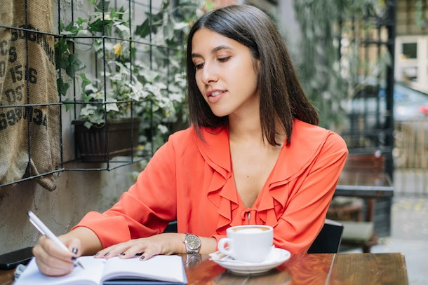 Young woman writing in notebook and drinking coffee