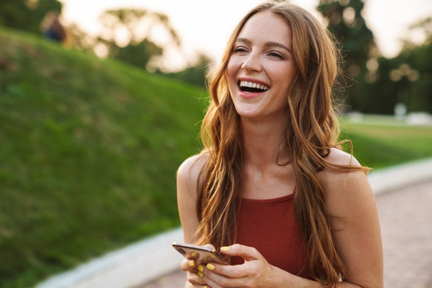 Photo of a happy laughing emotional young ginger woman walking in nature green park outdoors using mobile phone.