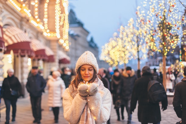 A woman wearing mittens, a sweater, and warm hat holds Christmas lights in the middle of a Connecticut holiday market.